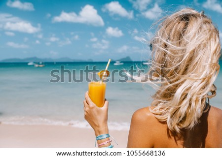 Back view of woman relaxing on the tropical beach, looking at sea landscape and drinking juice. Travelling tour in Asia: El Nido, Palawan, Philippines.