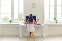 Back view of woman taking break from office work and meditating sitting in modern workspace at table with desktop computer and cup of coffee to go. Concepts of corporate wellbeing and stress relief