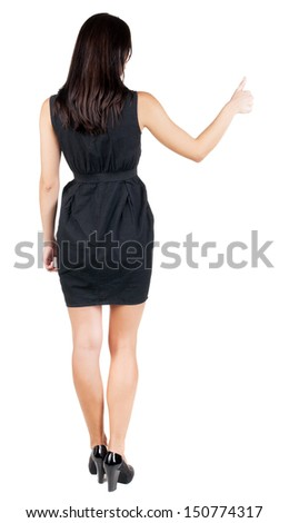 Back view of  woman thumbs up. Rear view people collection. backside view of person. Isolated over white background. slender brunette in a dress shows the symbol of success or hitchhiking