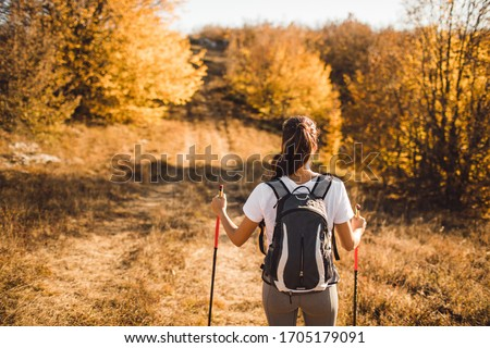 Back view of woman with backpack and trekking sticks. Nordic walking. and hiking. Autumn nature around and path forward. Travel concept. Photo stock ©