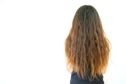 Back view of woman with her damaged split ended hair. Hair damage is risk for further damage and breakage. It may also look dull or frizzy and be difficult to manage.