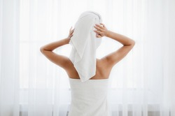 Back view of woman wrapped in towel standing next to window, drying her hair after morning shower