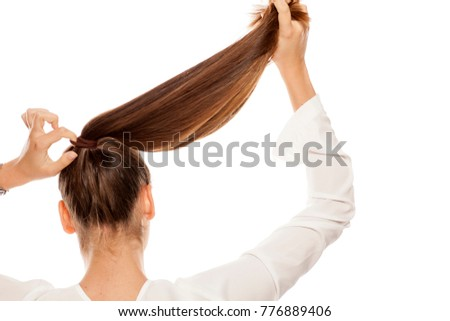 Back view of women that tightens the hair in a ponytail