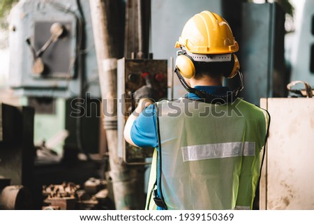Back view of Work at factory.Asian worker man  working in safety work wear with yellow helmet l ear muff.machanic male asia in factory workshop industry machine professional