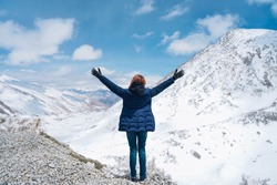 Back view of young asian woman traveler in dark blue jacket cheering open arms at mountain peak in Leh, Ladakh, India. Enjoying holidays. Amazing nature background.