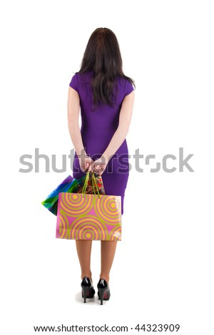 Back view of young beautiful woman with shopping bags looking at wall. The rear view.