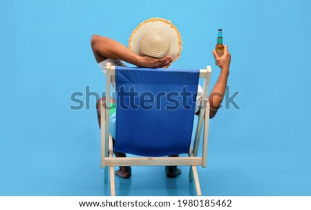 Back view of young black guy sitting in lounge chair with bottle of beer, enjoying summer vacation, sipping alcoholic beverage, sunbathing on blue studio background, full length