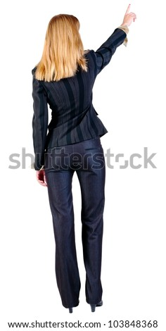 Back view of young blonde business woman pointing at wall. beautiful girl in dark suit. Rear view people collection. backside view of person. Isolated over white background.