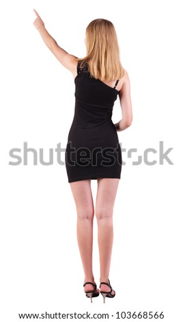 Back view of young blonde woman pointing at wall . beautiful girl in black dress showing gesture. backside view of person.  Rear view people collection. Isolated over white background.