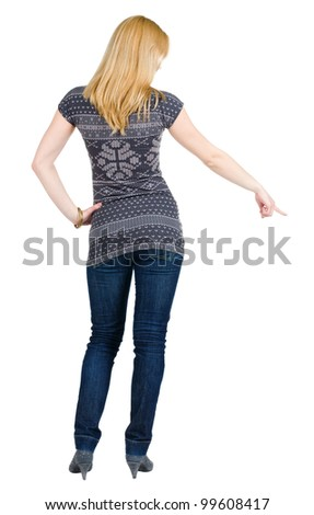 Back view of young brunette woman pointing at wall . beautiful girl in blue jeans and sweater showing gesture. Rear view. Isolated over white background.
