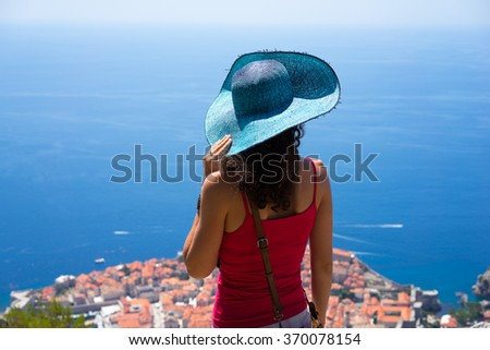 Back view of young brunette woman tourist in wide brim blue hat looking on Dubrovnik view from high mountain.