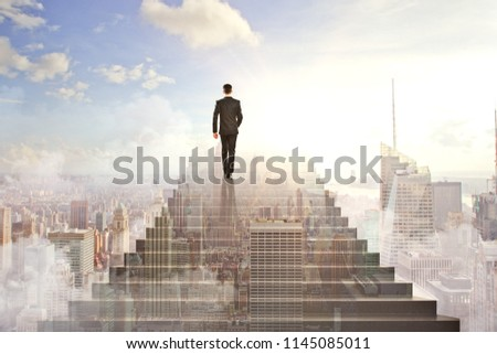Back view of young businessman climbing abstract stairs on city sky background. Success and growth concept. Double exposure