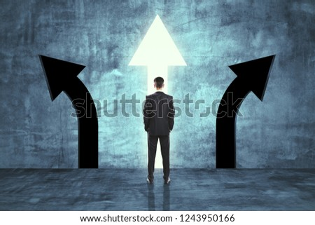 Back view of young businessman in concrete room with three arrows. Different direction and choice concept  #1243950166