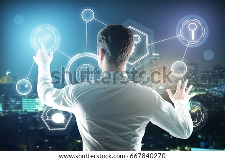Back view of young businessman managing business icons on night city background. Touchscreen concept #667840270