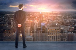 Back view of young businessman on concrete rooftop looking at city with setting sun. Research concept