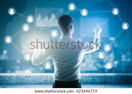 Back view of young businessman on rooftop managing business charts. Recruiting concept #623646719