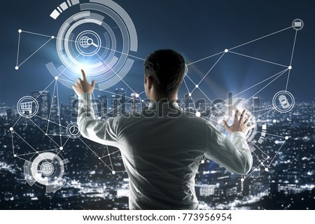 Back view of young businessman pointing at abstract digital business hologram on city background. Infograph and finance concept. Double exposure  #773956954