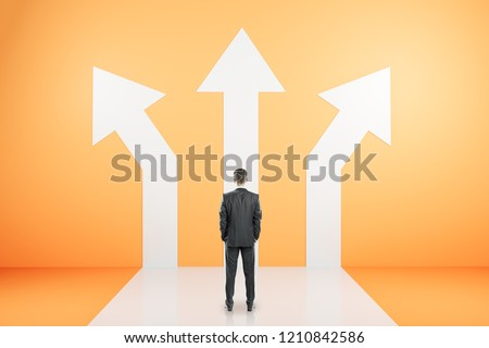 Back view of young businessman standing on orange background with three arrows. Different direction and success concept
