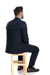 back view of young businessman thinking, sitting isolated on white background in studio