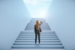 Back view of young businesswoman climbing abstract bright concrete sky stairs. Career development and growth concept