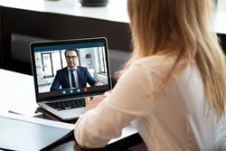 Back view of young businesswoman talk with male business partner using video call on modern laptop, female employee speak consult with businessman on webcam conference, online consultation concept