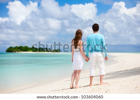 Back view of young couple at tropical beach
