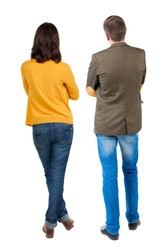 Back view of young couple man and woman hug and look into the distance. beautiful friendly girl and guy together. Rear view. Isolated over white background. young woman holds the hand of her husband