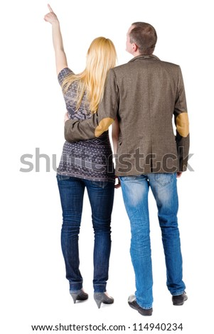 Back view of young couple pointing at wall. guy in the costume jacket and the girl in a sweater looking into the distance. Rear view. Isolated over white background. #114940234