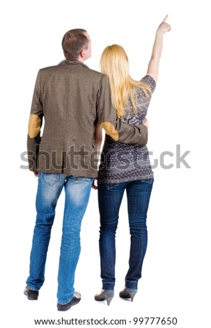 Back view of young couple pointing at wall. guy in the costume jacket and the girl in a sweater looking into the distance. Rear view. Isolated over white background.