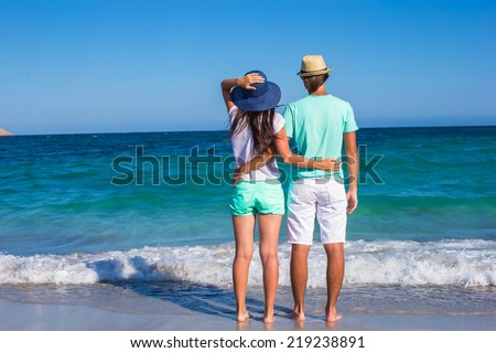Back view of young couple walking at beach during tropical vacation #219238891