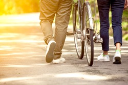 Back view of young couple walking  together with bicycle in the garden in vintage color tone