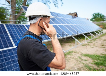 Back view of young engineer technician talking on cellphone standing in front of almost finished high exterior solar panel photo voltaic system in rural countryside on bright sunny summer day.