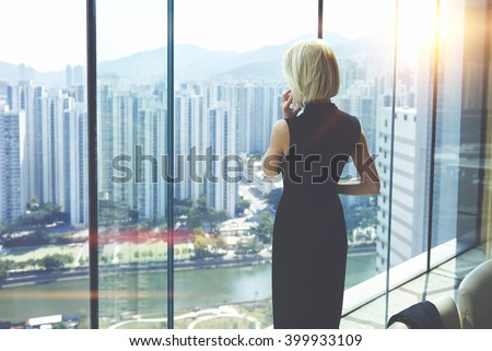 Back view of young entrepreneur is calling via cell telephone, while is standing in her private office against window with view of developed business district with high skyscrapers.Copy space for text