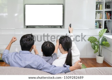 Back view of young family, man and woman watching TV together in living room, TV on white background