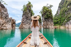 Back View of Young Female Tourist in Dress and Hat at Longtail Boat near Three rocks with Limestone Cliffs at Cheow Lan Lake. Woman on Boat in Ratchaprapha Dam Khao Sok National Park in Thailand
