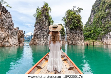 Back View of Young Female Tourist in Dress and Hat at Longtail Boat near Three rocks with Limestone Cliffs at Cheow Lan Lake. Woman on Boat in Ratchaprapha Dam Khao Sok National Park in Thailand ストックフォト ©