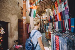 Back view of young female traveller at traditional bazaar in Dubai, UAE