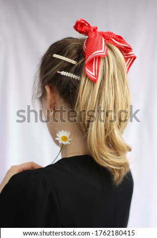back view of young girl in black dress with high ponytail pearl hairpins and red silk scarf Stockfoto ©