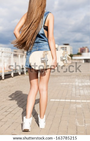 back view of young girl in short overalls with long legs and long silky hair holding skateboard