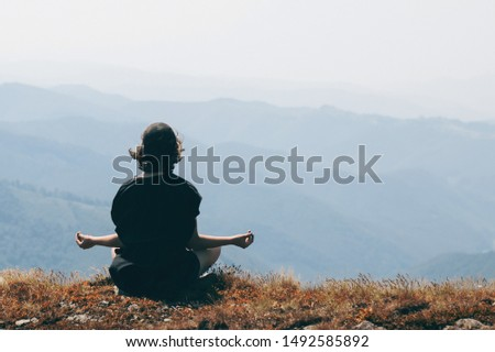 Back view of young girl sitting alone on edge of the mountain and meditating. Female enjoying stunning landscape. Woman practicing yoga, sits in easy pleasant pose. Working out outdoors. Copy space