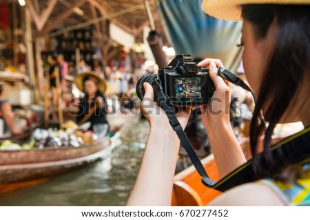 back view of young girl traveler using camera taking photo with local vendor when she taking on boat visiting Damnoen Saduak floating market of Thailand.
