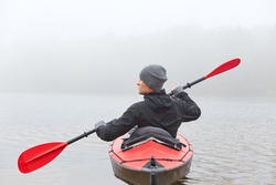 Back view of young handsome man kayaking in river, spends foggy morning in canoe, extreme sport, man in black jacket and gray cap rowing boat and looking aside.