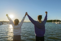 Back view of young happy couple on end of pier in Finland with arms raised looking at sunset