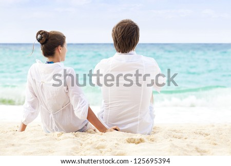 back view of young happy couple sitting on tropical beach. honeymoon concept