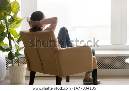 Back view of young happy woman sitting in comfortable armchair, facing shiny window, crossing hands behind head, having rest after housework, resting on weekend, lazy day concept.