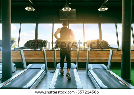 Back view of young man athlete with running on treadmill in gym.