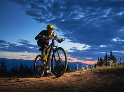 Back view of young man cycling bicycle under beautiful night sky. Male bicyclist in safety helmet riding on hillside road under blue cloudy sky in the evening. Concept of sport and active leisure.
