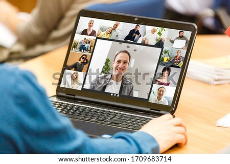 Back view of young man using headset and laptop and having videoconference at home