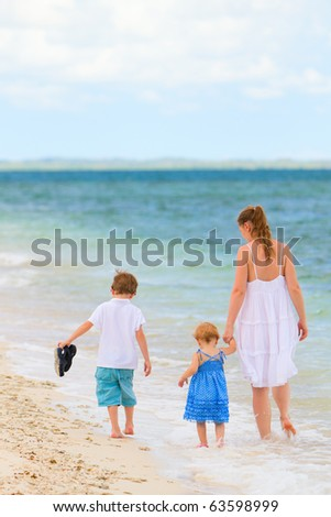 Back view of young mother and her two kids walking along tropical white sand beach