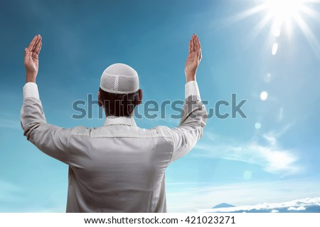 Back view of young muslim man praying